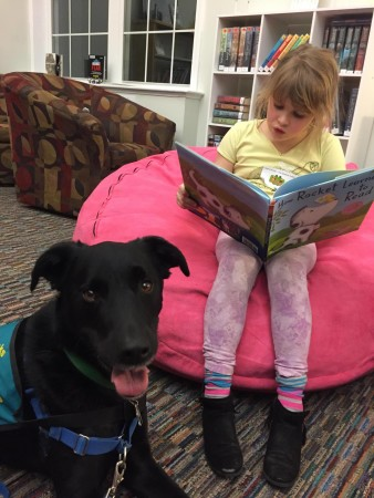 """Emily reads """"How Rocket Learned to Read"""" by Tad Hills to Koda-the-Sidekick at a recent Reader of the Pack session at Orono Public Library.  CREDIT: Photo courtesy Stacey Coventry."""