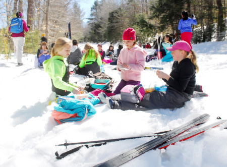 The fifth graders find a resting spot along the trail to eat lunch, before sking back to the Dedham School in Holden on Monday, March 20. Photo by Terry Farren.