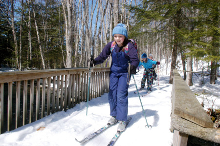 Fifth graders from the Dedham School in Holden ski across a bridge on the school trail. CREDIT: Photo by Terry Farren.